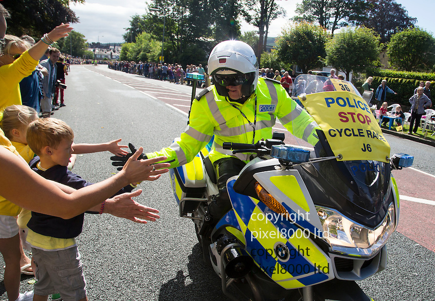 Grand Depart - Tour de France 2014<br /> Yorkshire England.<br /> Leaders go through famous town of Ilkley with Moors in distance.<br /> <br /> Fans get a high five from police motorcyclist <br /> Motorcycle cop clearing the way<br /> <br /> <br /> Pic by Gavin Rodgers/Pixel 8000 Ltd