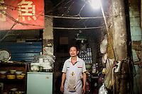 """Tong Su Chun, has been cooking at this small unnamed outdoor noodle cafe at the bottom of Shibati, or 18 Steps, in central Chongqing, for about 20 years. The shop is managed by his nephew.  The neighborhood is slated for redevelopment, and all residents, including this shop, must leave the area by October 2014. Tong Su Chun said he didn't know what he would do after the restaurant closes. """"I'll take a break,"""" he said, """"and then find something new."""" The restaurant typically serves a couple hundred people in a night, most spending about 15 RMB."""