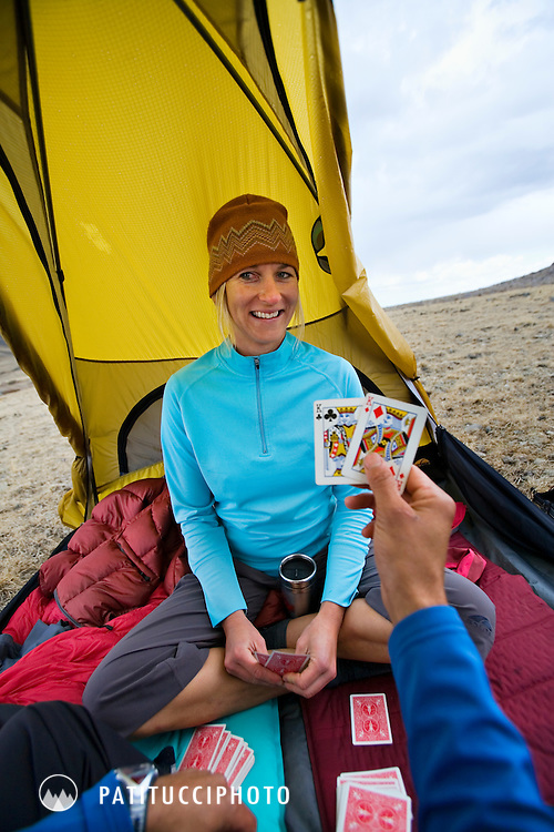 Keith Glidewell and Keri Davis playing cards while waiting out a rain storm during a backpacking trip in the White Mountains of California