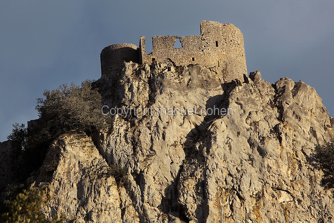 "Old keep of the Lower Castle, Peyrepertuse Castle or Chateau Pierre Pertuse, Cathar Castle, Duilhac-sous-Peyrepertuse, Corbieres, Aude, France. This castle consists of a Lower Castle built by the Kings of Aragon in the 11th century and a High Castle built by Louis IX in the 13th century, joined by a huge staircase. Its name means pierced rock in Occitan and it has been associated with the Counts of Narbonne and Barcelona. It is one of the ""Five Sons of Carcassonne"" or ""cinq fils de Carcassonne"" and is a listed monument historique. This view shows steep cliffs which act as natural defenses. Picture by Manuel Cohen"