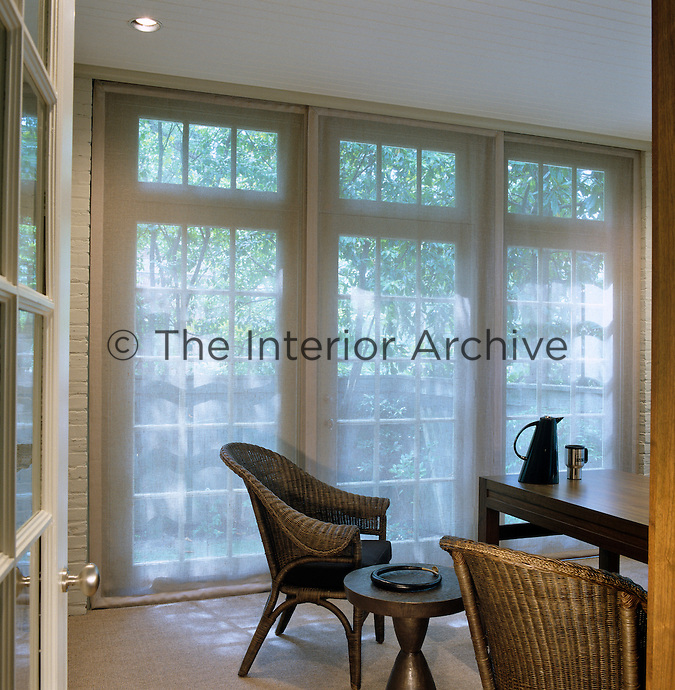 Sheer curtains diffuse the sunlight in the breakfast room which is furnished with contemporary Lloyd Loom wicker chairs