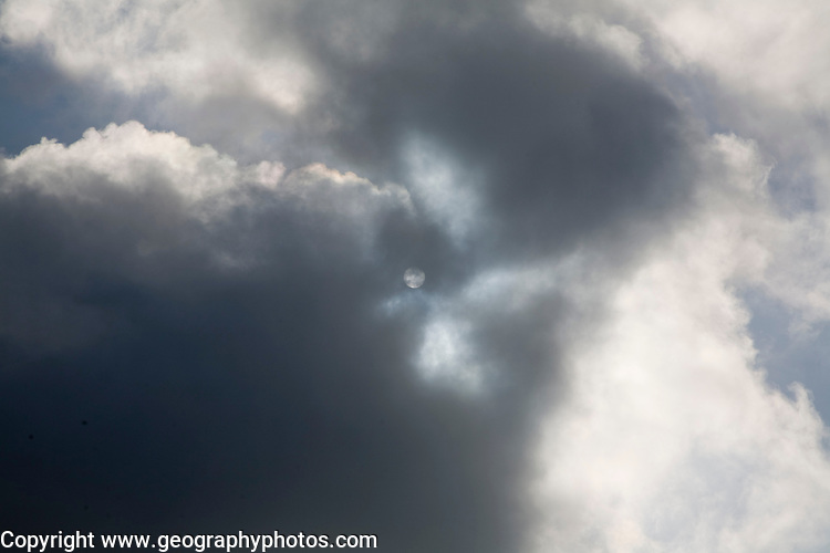 Sun surrounded by and partially obscured by cloud, UK