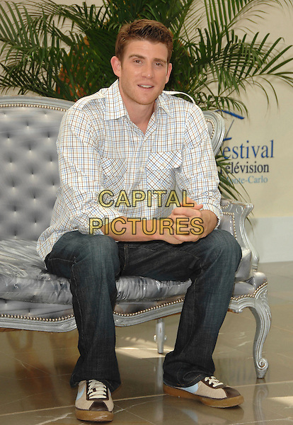 "BRYAN GREENBERG.attends a photocall promoting the television series ""October Road"" on the third day of the 2008 Monte Carlo Television Festival held at Grimaldi Forum in Monte Carlo, Principality of Monaco, June 10, 2008..full length sitting on sofa couch hands shirt jeans plaid checked white.CAP/TTL .©TTL/Capital Pictures"