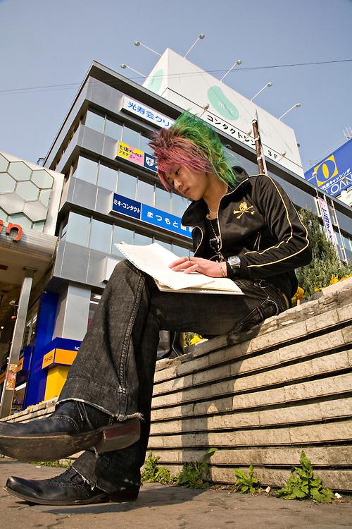 Japanese male punk rocker sitting outside Himeji Station in Himeji Japan