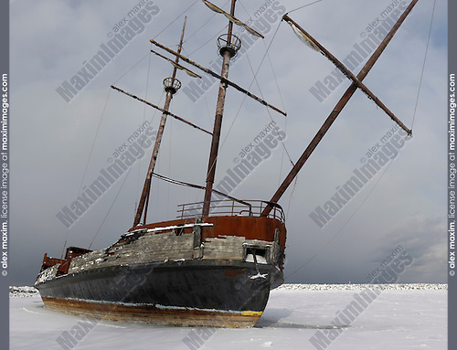 Rusting grounded ship in frozen water under dramatic gloomy sky wintertime scenic