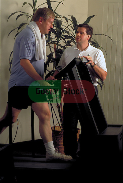 personal trainer monitoring man on exercise machine