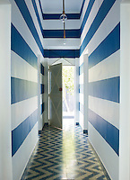 A minimal blue and white entrance hall lined with cement tiles by Popham Design. Stripes and zig zag patterns create a striking effect.