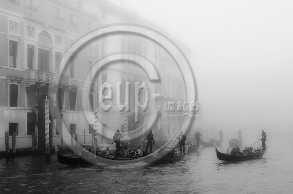 Venice-Italy - January 16, 2011 -- A group of gondolieri / gondoliers on tour with tourists on Grand Canal / Canal Grande in the early morning winter mist, gondola -- tourism, infrastructure, transport, water, b&w -- Photo: Horst Wagner / eup-images