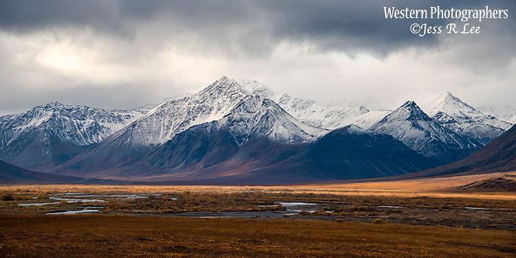 A photo of the Brooks Range in Alaska with snow covered peaks and fall colored tundra.