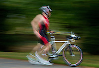 28 SEP 2014 - STOWMARKET, GBR - A competitor runs  from transition to the mount line as he prepares to start on the 18km bike during the 2014 West Suffolk Triathlon in Stowmarket in Suffolk, Great Britain (PHOTO COPYRIGHT © 2014 NIGEL FARROW, ALL RIGHTS RESERVED)
