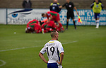 Barrow AFC 0 Newport County 3, 15/09/2012. Furness Building Society Stadium, Football Conference. Home defender Tom Aldred (foreground) looks on in dejection as the visitors celebrate their crucial second goal at Barrow AFC's Furness Building Society Stadium during the Barrow (white shirts) v Newport County Conference National Fixture. Newport County eventually won the match by 3-0, watched by 802 spectators. Both Barrow and Newport County from Wales were former members of the Football League in England. Photo by Colin McPherson.