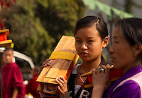 Buddhist devotees carrying holy scrolls during the ceremonial procession at a monastery in Sikkim, India