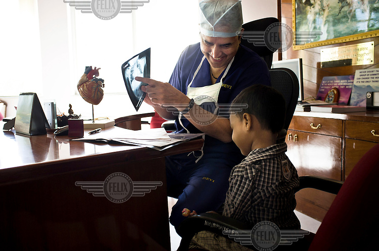 Heart surgeon, Dr. Devi Prasad Shetty (58), shares a light moment while looking at an x-ray with a young patient during a consultation in his office at the Narayana Hrudayalaya hospital.