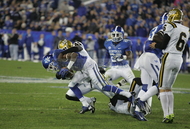 UK wide receiver Demarco Robinson (9) strains against the hold of Alabama State linebacker Marquis Lovett (41) during UK's homecoming game vs. Alabama State at Commonwealth Stadium in Lexington, Ky., on Saturday, November 2, 2013. Photo by Adam Pennavaria | Staff