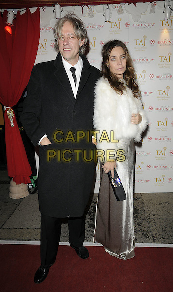 SIR BOB GELDOF & JEANNE MARINE .At the Royal Rajasthan gala dinner, Banquetting House, Whitehall, London, England, UK, November 9th 2009..full length black coat tie couple white fur coat jacket silk satin silver long maxi dress clutch bag hands in pockets .CAP/CAN.©Can Nguyen/Capital Pictures.