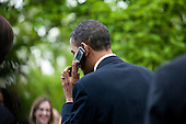United States President Barack Obama talks on the cell phone of an audience member after giving remarks at an Earth Day reception in the Rose Garden at the White House in Washington, D.C., U.S., on Thursday, April 22, 2010. .Credit: Brendan Hoffman - Pool via CNP