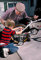 A six-year-old boy turns wrench to put training wheels on as grandfather holds the bike. child and grandfather.