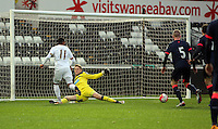Pictured: Kenji Gorre of Swansea (L) passes the ball past goalkeeper Nathan Harker, to team mate Jay Fulton who scored the first goal Monday 04 April 2016<br />