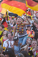 Germany, DEU, Dortmund, 2006-Jun-24: FIFA football world cup (USA: soccer world cup) 2006 in Germany; German football fans in good mood at a public viewing zone during the world cup match Germany vs. Sweden (2:0). A young woman sitting on two men's shoulders is waving a German flag.
