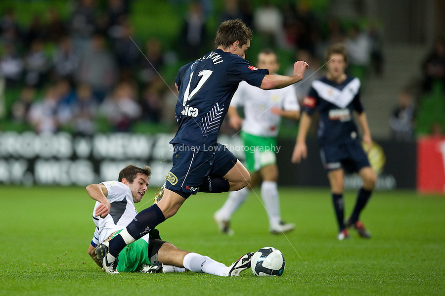 MELBOURNE, AUSTRALIA - May 14, 2010: MATTHEW FOSCHINI from Melbourne Victory avoids a tackle from Michael Zullo of the Come Play XI at the in Kevin Muscat Testimonial match between the Melbourne Victory and Come Play XI at AAMI Park on May 14, 2010 in Melbourne, Australia. Photo Sydney Low www.syd-low.com