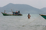 CAMBODIA  -  APRIL 3, 2005:  A tourist swims between boats off the shore of Rabbit Island on April 3, 2005 Cambodia.  Kep can be seen on the other side of the water.  (PHOTOGRAPH BY MICHAEL NAGLE)