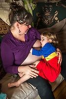 """A woman  8 months pregnant breastfeeds her little girl aged 3 years old on a sofa in the living room.<br /> <br /> Image from the """"We Do It In Public"""" documentary photography project collection: <br />  www.breastfeedinginpublic.co.uk<br /> <br /> Dorset, England, UK<br /> 14/02/2013"""