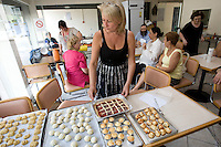 Laure Boutboul (C) sets out freshly baked pastries during an Oriental pastry workshop held by the non-profit association Batisseusses de Paix (or Women Peace Builders) that seeks to build ties between Muslim and Jewish women, in her restaurant in Creteil, outside Paris, France, 24 June 2008.