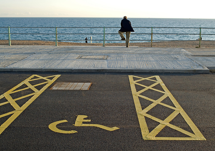 A man leans on railings on the seafront at Brighton Marina, next to parking space reserved for disabled users.