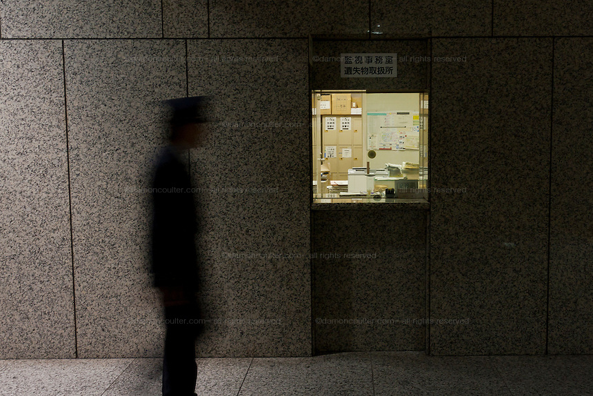 A security guard walks by a window for the security office inside the Tokyo Metropolitan Government Building corridors. Shinjuku, Tokyo, Japan. Friday November 11th 2011