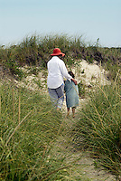 Girl wrapped in a beach towel walking through dune grass with her grandmother, Brewster, Cape Cod, MA<br />