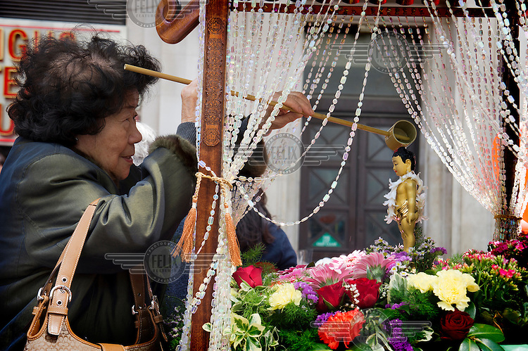 A woman pours water on a Buddha figurine, symbolically purifying herself, during celebrations held in London's Leicester Square to mark Buddha's birthday.
