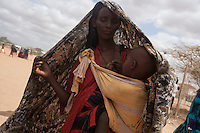Kenya - Dadaab - A Somali mother carries her child.