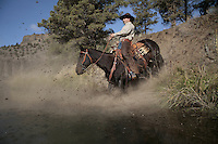 Rick Lauman rides down a steep embankment on his mustang.  Sure-footed and trusting, the horse is loyal to Lauman.<br />