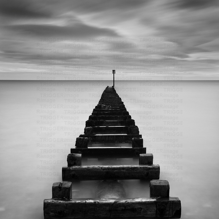 Wooden groyne sea defences leading to horizon