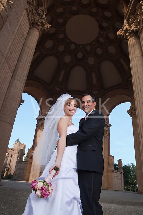 USA, California, San Francisco, bride and groom embracing under arches