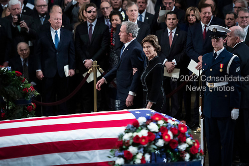 WASHINGTON, DC - DECEMBER 3 : Former president George W. Bush and wife Laura Bush look back at former president George H.W. Bush as he lies in State at the U.S. Capitol Rotunda on Capitol Hill on Monday, Dec. 03, 2018 in Washington, DC. (Photo by Jabin Botsford/Pool)