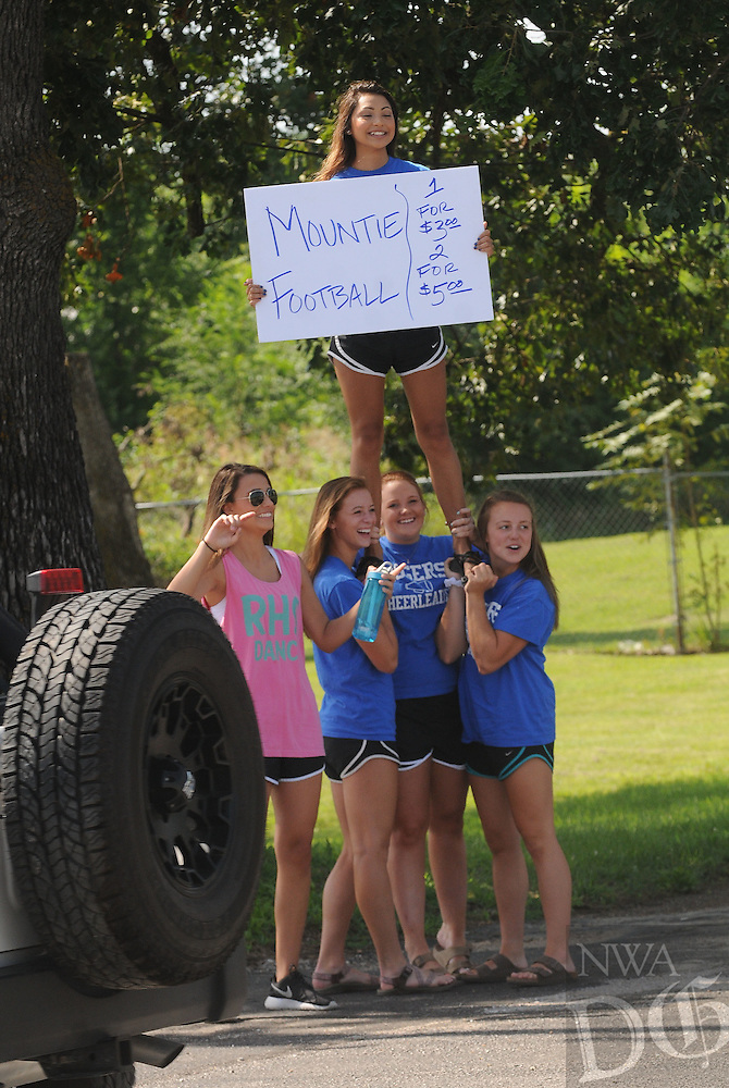 NWA Democrat-Gazette/FLIP PUTTHOFF<br /> THREE CHEERS FOR CHICKEN<br /> Rogers High School cheeleaders Alie Thompson (top) and Samantha Haley (from left) Hannah Lueders, Maggie Mankin and Kirsten James, beckon motorists to buy barbecued chicken on Saturday July 11 2015 during a barbecue to benefit the Rogers Mountaineers football team. Whitey's Chicken Cookin' Crew barbecues and sells chicken as a fundraiser for various groups most Saturdays near Second and Locust streets in downtown Rogers.