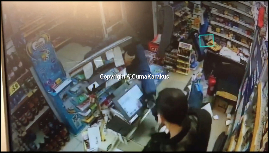 BNPS.co.uk (01202 558833)<br /> Pic: CumaKarakus/BNPS<br /> <br /> The moment the robber lunges for Cuma.<br /> <br /> This is the dramatic movement a heroic shopkeeper scared off a knife-wielding raider by launching a glass jar of dog biscuits at him. <br /> <br /> Brave Cuma Karakus dodged the masked thug's eight inch blade as he jabbed over the counter armed only with the treats he keeps for customers' pets. <br /> <br /> The dad of two then incredibly threw it at the crook as he tried to run around the table, appearing to hit a glancing blow on his hand.