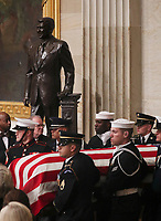 A U.S. military honor guard carries the casket of former U.S. President George H.W. Bush past the statue of former President Ronald Reagan as it arrives to lie in state in the U.S. Capitol Rotunda in Washington, U.S., December 3, 2018. <br /> CAP/MPI/RS<br /> &copy;RS/MPI/Capital Pictures