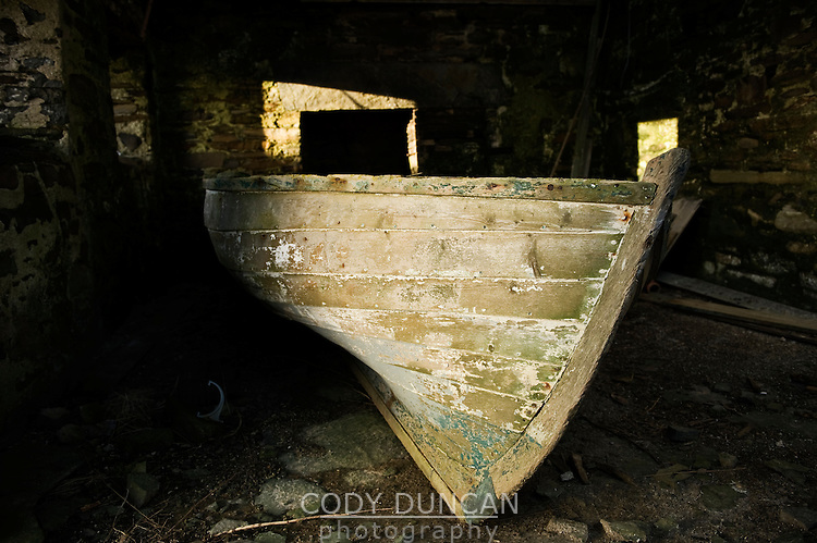 Old boat sits in barn of abandoned house, South Ronaldsay, Orkney, Scotland