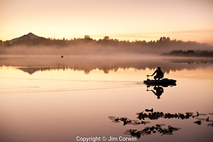 Sunrise in fog Lake Cassidy with fishermen in small fishing boat