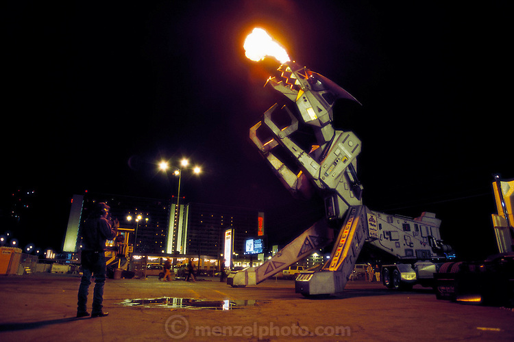 Flames shoot from the jaws of Robosaurus, the human-piloted car-crushing entertainment robot. Robosaurus stands 12 meters high (36 feet), weighs 26 tons and its jaws have a crushing force of nine tons. It uses this force to crush and tear cars to bits for entertainment. Robosaurus was created by American inventor Doug Malewicki. Generally machines are considered robots if they are at least semi-autonomous or remotely controlled. Robosaurus is not. Nevada, USA