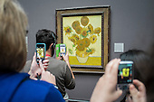 Visitors to the National Gallery in London take pictures of Van Gogh's Sunflowers following the lifting of restrictions on the use of smartphones and cameras.