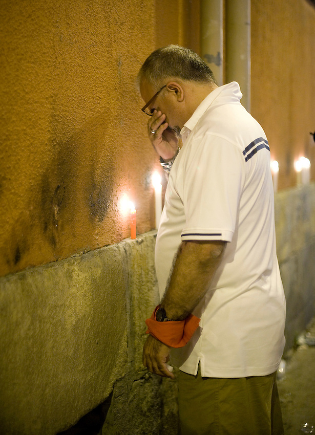 Revellers pray next to candles near Pamplona's Council Square at the end of the San Fermin festival on July 15, 2013, in Pamplona, Basque Country. On each day of the eight San Fermin festival days six bulls are released at 8:00 a.m. (0600 GMT) to run from their corral through the narrow, cobbled streets of the old navarre town over an 850-meter (yard) course. Ahead of them are the runners, who try to stay close to the bulls without falling over or being gored. The San Fermin Festival was made famous by the novel of U.S. writer Ernest Hemmingway called 'The Sun Also Rises.' (Ander Gillenea / Bostok Photo)