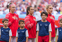 PARIS,  - JUNE 28: Becky Sauerbrunn #4, Kelley O'Hara #5 and Abby Dahlkemper #7 stand for the national anthem during a game between France and USWNT at Parc des Princes on June 28, 2019 in Paris, France.