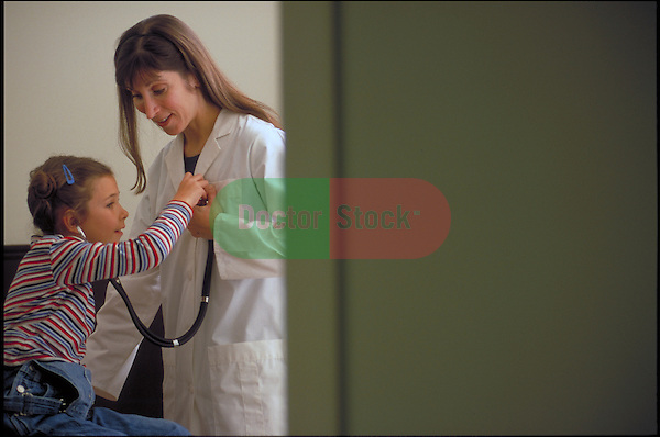 young girl patient examining doctor's chest with stethoscope
