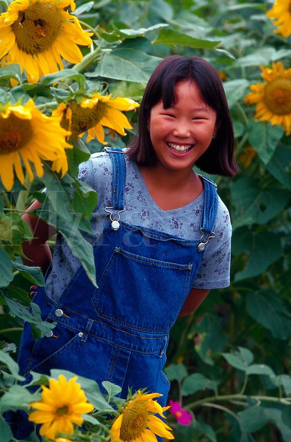 Girl amidst sunflowers.