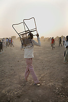 At the end of the day's action a spectator carries his chair back to his village during the Twic Olympics in Wunrok, Southern Sudan.