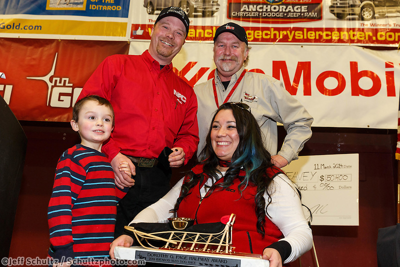Gary Samuelson and Mercie McGuffey present the GCI Dorothy G. Page halfway award to Aaron Burmeister, along with his son Hunter, at the musher 's finishers banquet in Nome on Sunday March 16 after the 2014 Iditarod Sled Dog Race.<br /> <br /> PHOTO (c) BY JEFF SCHULTZ/IditarodPhotos.com -- REPRODUCTION PROHIBITED WITHOUT PERMISSION