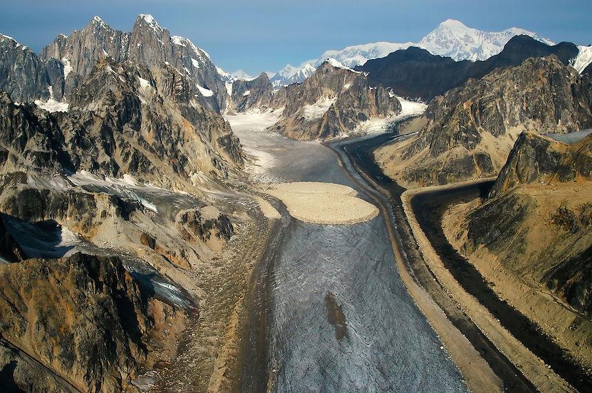 Oblique aerial view of landslide debris on the Buckskin Glacier with the Moose's Tooth (10,335 ft) and Mount McKinley aka Denali (20,320 ft) in the background, Denali National Park and Preserve, Alaska Range, Alaska, United States.